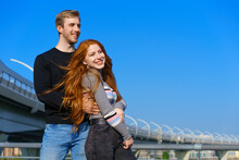 Happy Young Couple Man And Woman With Long Red Hair, Stand Against The Background Of A Blue Sky And A Bridge In Casual Clothes And Smile. Cheerful Guy And Caucasian Girl On A Sunny Day
