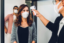 Group Of Professional Asian Business And Using Infrared Thermometer For Checking Body Temperature Staff Fever Before Work In Quarantine For Coronavirus Wearing Protective Mask At Office
