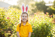 Smiling School Kid Outside In Garden Wearing Rabbit Ears For Easter Celebrations
