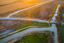 Aerial View Of A Country Road Crossing An Irrigation Channel At Sunset