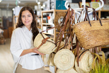 Young Positive Woman Customer Standing With Wicker Bag In Shop For Decor