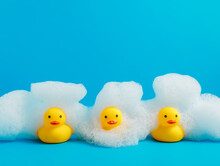Three Little Rubber Ducklings In A Row Covered With Foamy Shampoo On A Vibrant Blue Background. Rubber Toys For Kids, Showers And Shampoos. Creative Bathing Concept.