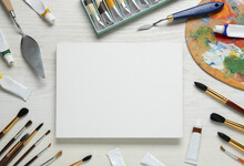 Blank Canvas, Tools, Palette And Paints On White Wooden Table, Flat Lay. Space For Text