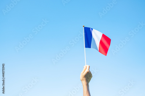 Fotografie, Obraz hand holding France flag on blue sky background