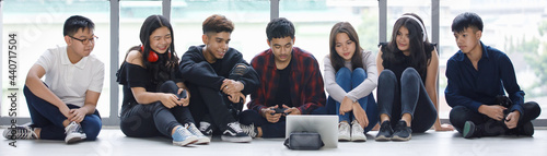 Photo Group of seven young male and female teenagers in casual clothes sitting on the floor and looking at the tablet screen with attractive smiling