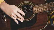 Close-up Shot Of A Young Female Musician Hands Playing Acoustic Guitar. Selective Focus On Guitarist's Hands. Guitarist Playing Music At Home