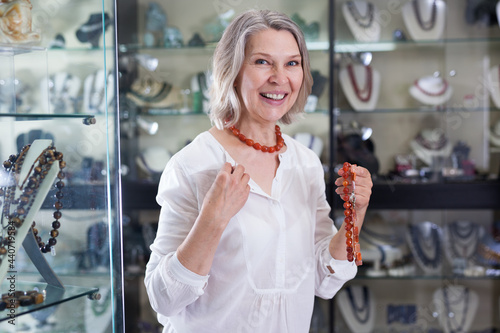 Fotografie, Obraz Woman chooses cornelian agate jewelry in boutique