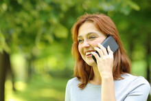 Happy Woman Talking On Smart Phone In A Park