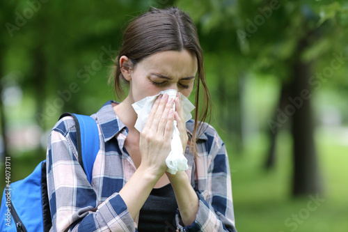 Fotografie, Obraz Student blowing on tissue in a park