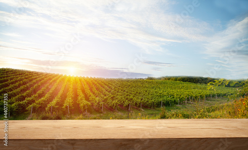 Fotografiet Brown wood table in autumn vineyard scenery against sunset sky with blank copy space on table for product display mockup