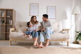 Happy family with little daughter sitting on sofa in living room