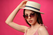 Leinwandbild Motiv Studio fashion portrait of a young attractive woman in hat and glasses against pink backgorund