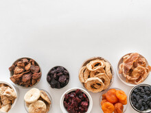 Flat Lay Various Dried Fruits And Berries In Bowls On White Background Vegan Healthy Natural Snacks.