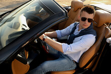 Handsome Young Man In Luxury Convertible Car Outdoors