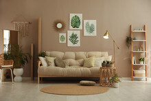 Stylish Living Room Interior With Comfortable Sofa And Beautiful Pictures On Wall