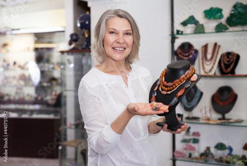 Fotografie, Obraz Female seller demonstrates cornelian agate necklace