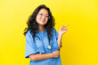 Leinwandbild Motiv Young surgeon doctor asian woman isolated on yellow background pointing finger to the side
