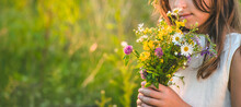Child Girl With Wildflowers In Summer. Selective Focus.