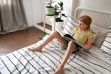 A Blond Boy In A Yellow T-shirt Reads A Book While Lying On The Bed