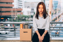Stressed And Worried Young Asian Woman With Box Of Items Sitting Alone After Being Laid Off From Job Due To Recession And Economic Stress In Industry