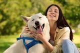 Fototapeta Zwierzęta - Teenage girl hugging her white Swiss Shepherd dog in park