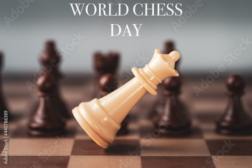 Fotografering white chess queen falling on chess board world chess day .