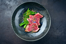 Modern Style Baby Broccoli With Fried Dry Aged Sliced Beef Fillet Steak Served As Top View On A Nordic Design Plate