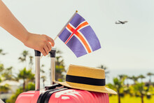 Woman With Pink Suitcase And Iceland Flag Standing On Passengers Ladder And Getting Out Of Airplane Opposite Sea Coastline With Palm Trees.