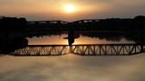 Zachód słońca nad rzeką przy moście kolejowym.