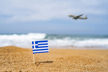 Flag Of Greece In The Form Of A Toothpick In The Sand Of Beach Opposite Sea Wave With Landing Airplane. Travel Concept