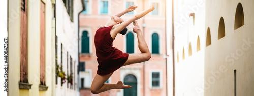 Fotografia Ballet dancer jumps through the streets of the city.
