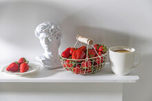 White Metal Basket With Wooden Handle With Fresh Strawberries, Corrugated Ceramic Cup Of Tea, Plaster Apollo Head On A Beige Table. Still Life.