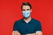 Leinwandbild Motiv Handsome young man in protective face mask looking at camera while standing against red background