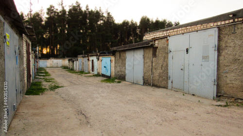 Fotografie, Obraz Garages and forest with sunset