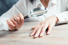 Woman Looking At Nails With A Magnifying Glass
