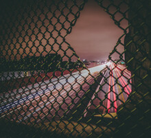 Long Exposure Traffic At Night Through A Hole In The Fence