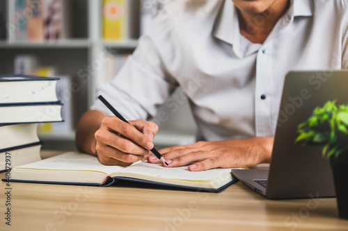 Human read books to increase knowledge. Student in glasses making notes writing down information from book in  library. Education learning concept with opening book or textbook in old library.