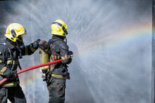 Two Fireman Or Firefighters Stand And Help Each Other To Spray Of Water With Curtain Shape And Rainbow Reflex Occur On Water Aerosol In Front Of Container Containing Fire Inside.