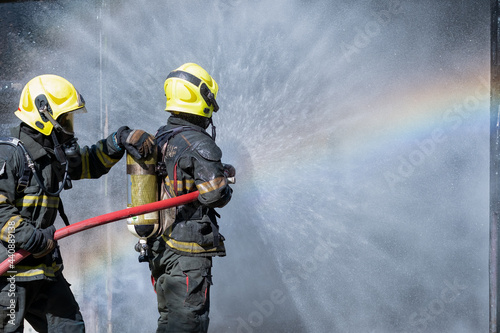Photo Two fireman or firefighters stand and help each other to spray of water with curtain shape and rainbow reflex occur on water aerosol in front of container containing fire inside