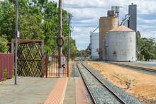 Looking Along A Rural Railway Platform, Down The Railway Line At Grain Silos