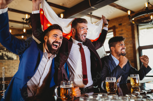 Fotografie, Tablou Men fans screaming and watching football on TV and drink beer in a pub