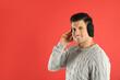 Leinwandbild Motiv Man wearing stylish earmuffs on red background. Space for text