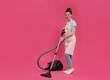 Leinwandbild Motiv Housewife with vacuum cleaner on pink background