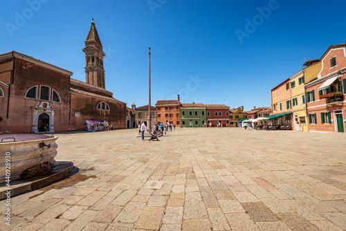 Slika na platnu Main square in Burano island, Piazza Baldassarre Galuppi, with the Parish church of San Martino Vescovo (Saint Martin Bishop) and the leaning bell tower (XVI century)
