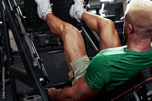 Fotografie, Obraz A man, a bodybuilder does exercises on his legs