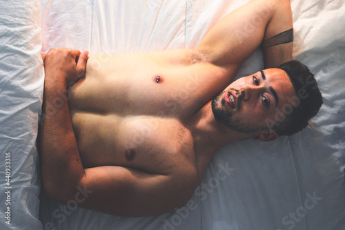 Young sexy caucasian man naked on the bed from a zenithal angle