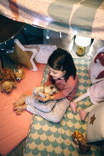 Top View Of Lovely Girl In Pajamas Playing With Stuffed Animal In A Teepee On Play Mats