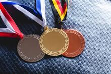 Gold, Silver And Bronze Medal On Velvet Cushion