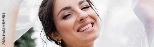 Foto Cheerful bride holding white veil outdoors, banner