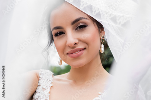 Canvas Smiling bride looking at camera near blurred white veil